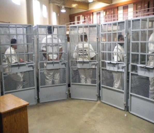 In this photo taken as part of federal litigation over California prison conditions, prisoners await a group therapy session at Mule Creek State Prison. How could being confined in tiny cages dissuade prisoners from committing suicide? – Photo filed in U.S. District Court briefings. Caption and photo are both copied from San Francisco Bay View's article, Motion Denied, Governor: Medical neglect is still killing prisoners, http://sfbayview.com/2013/motion-denied-governor-medical-neglect-is-still-killing-prisoners/